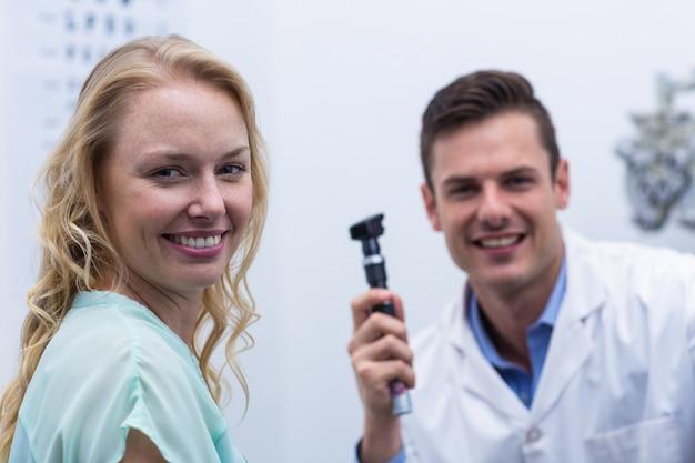 Женский пациент улыбается с окулистом в фоновом режиме
