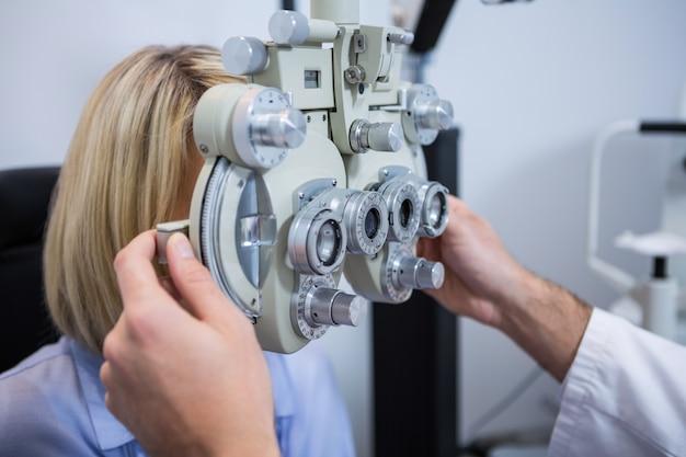 Пациентка проходит проверку зрения через фороптер