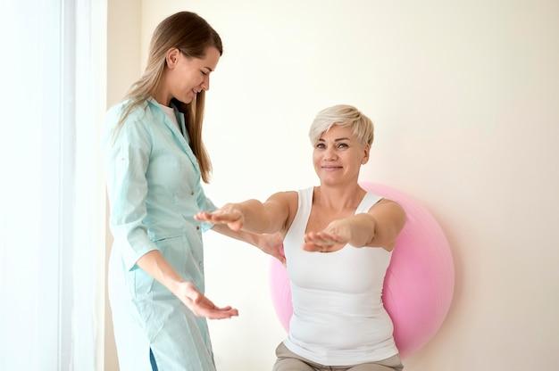 물리 치료사와 치료를 받고있는 여성 환자