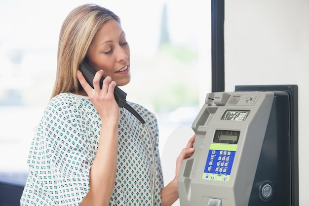 Female patient using payphone