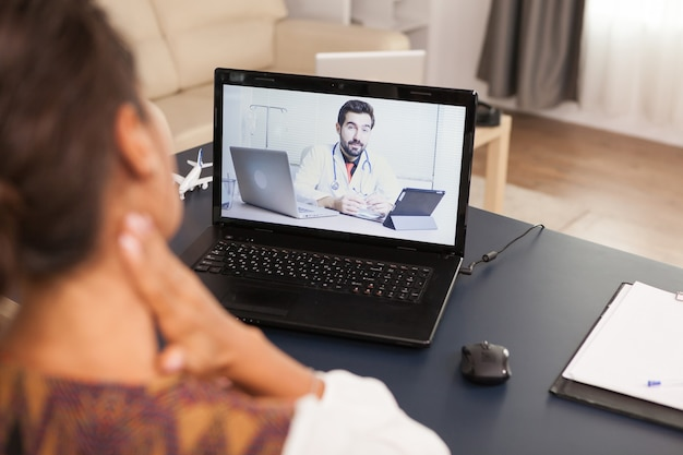 Female patient in a video call with doctor talking about her neck injuri.