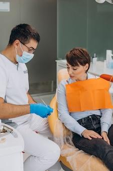 クリニックで歯科医を訪問している女性患者