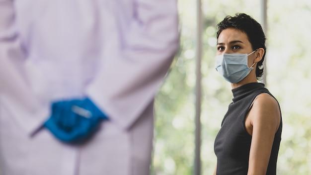 여성 환자는 얼굴 마스크를 착용하고 앉아서 흰색 실험실 가운과 파란색 고무 장갑을 낀 의사가 흐릿한 전경에서 백신 주사기 바늘을 손에 들고 숨깁니다.