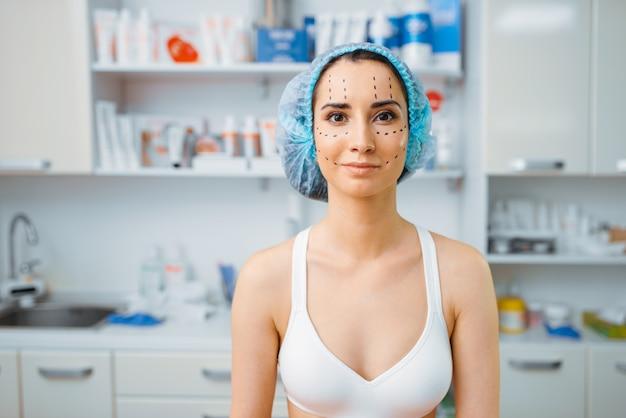彼女の顔、美容師のオフィスにマーカーを持つ女性患者。美容サロンでの若返りの手順。しわに対する美容整形、ボトックスへの準備