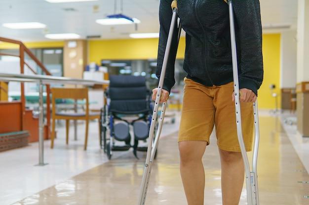 Женские пациенты тренируются с костылями в больнице.