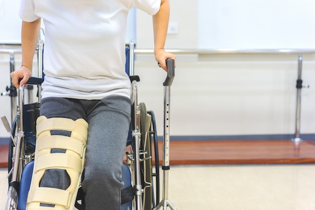 Female patients wear knee support devices to reduce movement while getting up from the wheelchair.