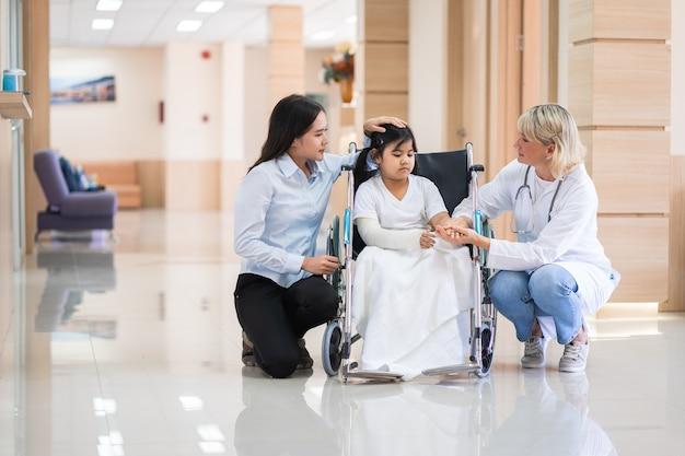 건강 의료 센터에서 그녀의 어머니와 휠체어에 여성 소아과 의사와 어린이 환자 프리미엄 사진