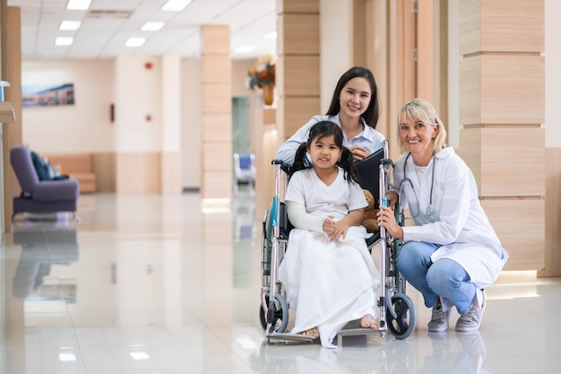 Female pediatrician doctor and child patient on wheelchair with her mother in the health medical center