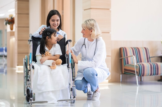 Female pediatrician doctor and child patient on wheelchair with her mother