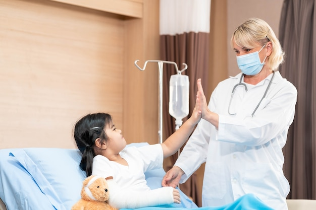Female pediatrician doctor and child patient with teddy bear in the health medical center