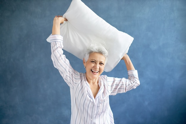 Female pensioner wearing silky pajamas laughing, being in good mood while having fun in bedroom, raising arms, holding feather pillow above her head