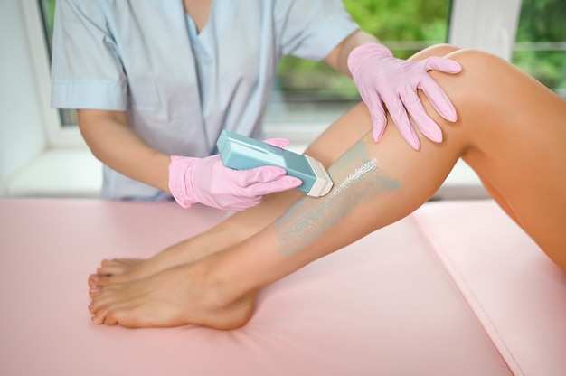 Female perfect legs with smooth skin having wax stripe depilation hair removal procedure in beauty salon by beautician
