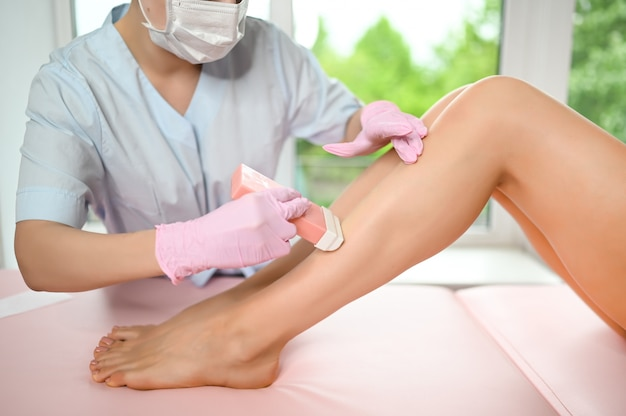 Female perfect legs with smooth skin having wax stripe depilation hair removal procedure on legs