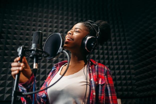 Female performer in headphones songs in audio recording studio.
