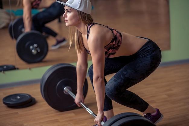 무게 막대와 데드 리프트 운동을 수행하는 여성. 체육관에서 역도 운동을하고 자신감을 젊은 여자