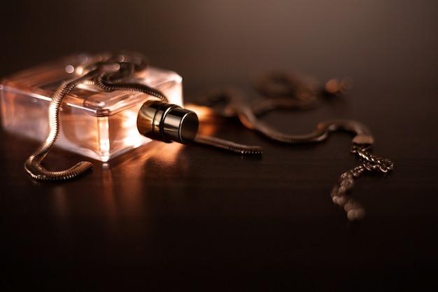 女性の香水と金のネックレス