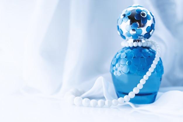 パールビーズと明るい表面上の女性の香水