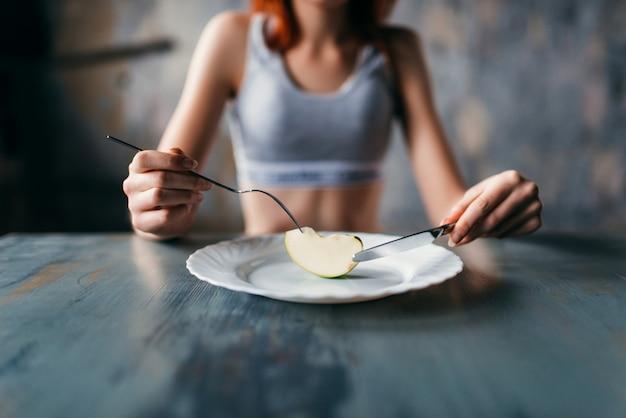 Женщина против тарелки с ломтиком яблока. концепция диеты для похудения