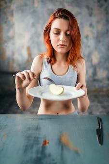 Женщина против тарелки с ломтиком яблока