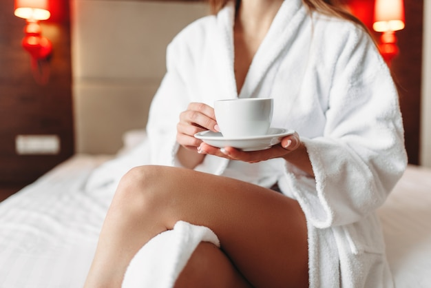 Female person in bathrobe holds in hand a cup of coffee, good morning concept.