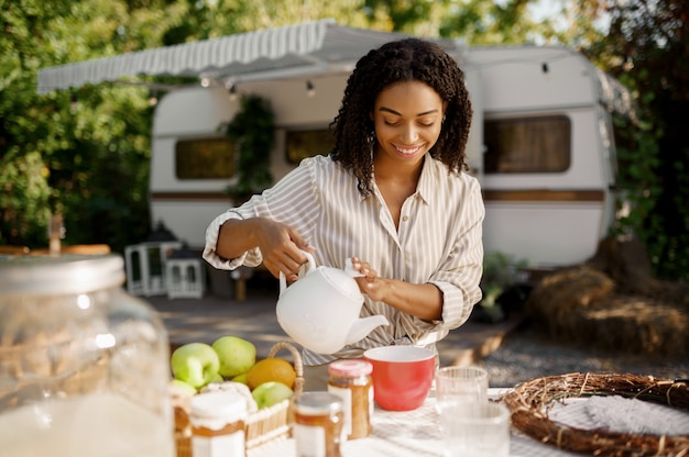 Rv, 트레일러 캠핑 근처에서 아침 식사를 요리하는 여성 사람. 커플 여행 밴, 캠핑카 휴가