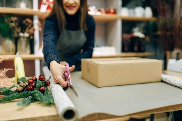 Женщина режет оберточную бумагу ножницами, украшение подарочной коробки. женщина обертывает подарок на столе, процедура декора ручной работы