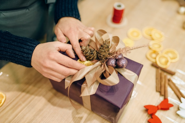Женщина украшает новогоднюю подарочную коробку еловой шишкой, вручную упаковывая и украшая. женщина обертывает подарок на столе, процедура декора