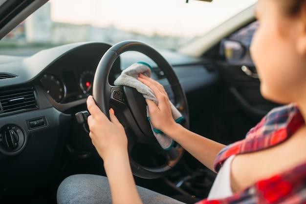 Женщина делает влажную уборку салона автомобиля на автомойке