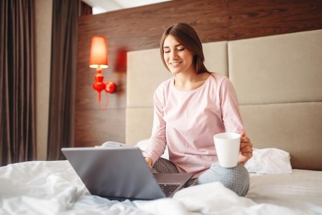 Женщина пьет кофе и использует ноутбук в постели