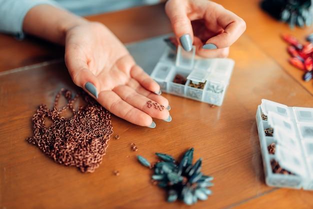 Руки лицо женского пола держит маленькие металлические кольца, мастер на работе. украшения ручной работы. рукоделие, изготовление бижутерии
