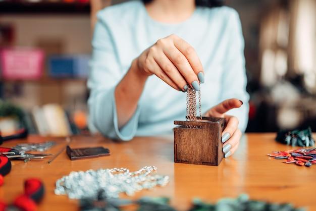 Женщина руками вытаскивает металлическую цепь из деревянного ящика, мастер за работой. украшения ручной работы. рукоделие, изготовление бижутерии