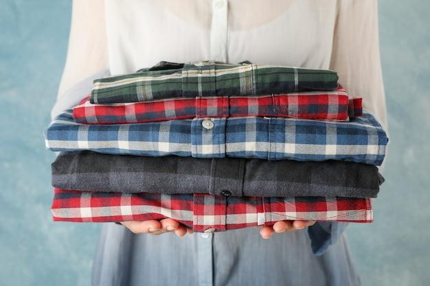女性の人は折り畳まれたシャツを保持、クローズアップ