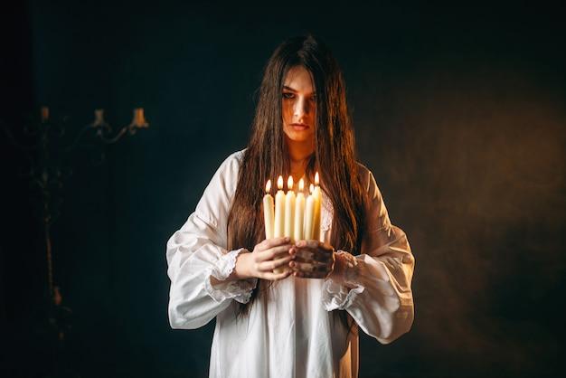 Женщина держит в руках свечи, гадание