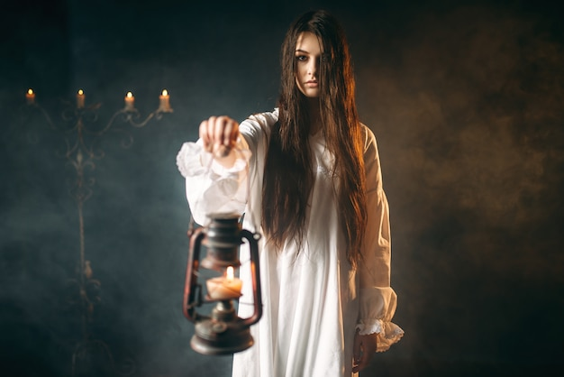 Female person holds kerosene lamp, dark magic