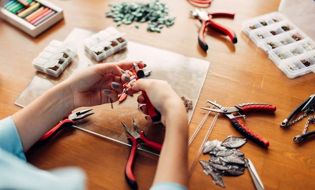 Женщина держит плоскогубцы, изготовление бижутерии
