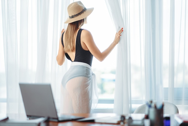 Женщина в купальнике смотрит в окно в офисе