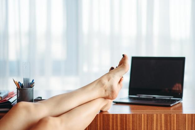 テーブルの上の女性の人の足、休暇の概念についての夢、空想の旅