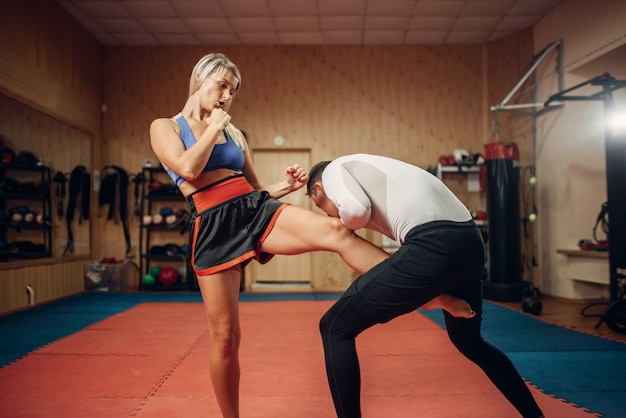 Female person makes a kick in the groin, self defense workout with male personal trainer, gym interior. woman on training, self-defense practice