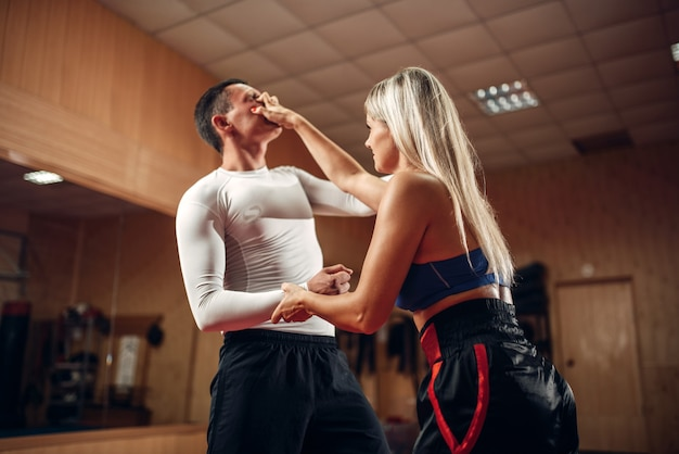 Female person makes pain in the eyes, self-defense workout with male personal trainer, gym interior. woman on self defense training