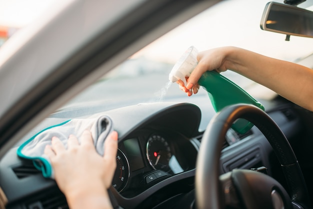 여성 사람은 자동차의 대시 보드를 연마하고 세차 과정을 연마합니다. 셀프 서비스 세차장에 아가씨. 여름날 야외 차량 청소