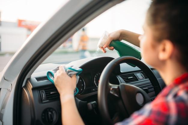 Женщина полирует приборную панель автомобиля