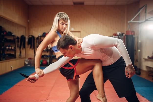 Женщина практикует удар коленом в живот