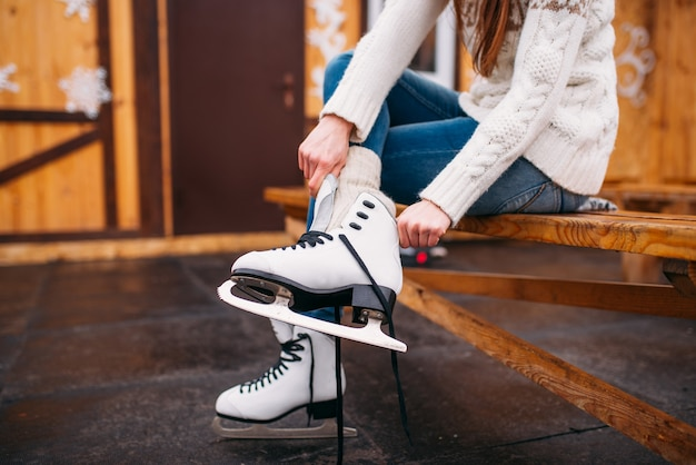 Female person sitting on bench and wears figure skates, skating rink. winter ice-skating, active leisure, sport activity