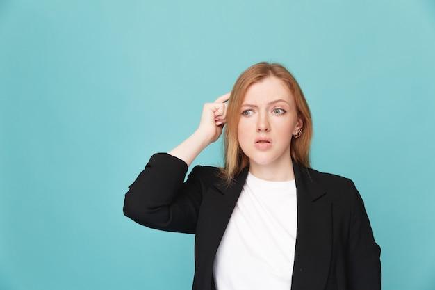 青いスタジオで混乱して立っている女性。