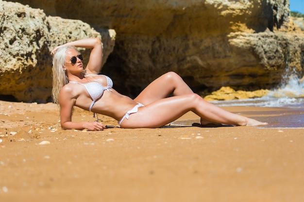 野生の岩のビーチで日光浴をしている女性
