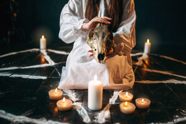 Female person in white shirt holds animal skull in hands, pentagram circle with candles. dark magic ritual, occultism