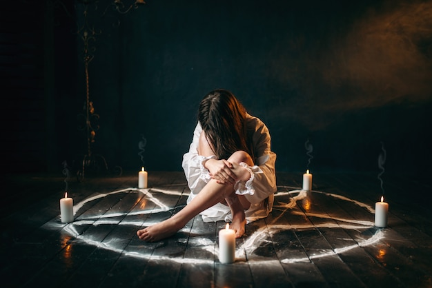 Female person in white shirt sitting in pentagram circle with candles. dark magic ritual, occultism