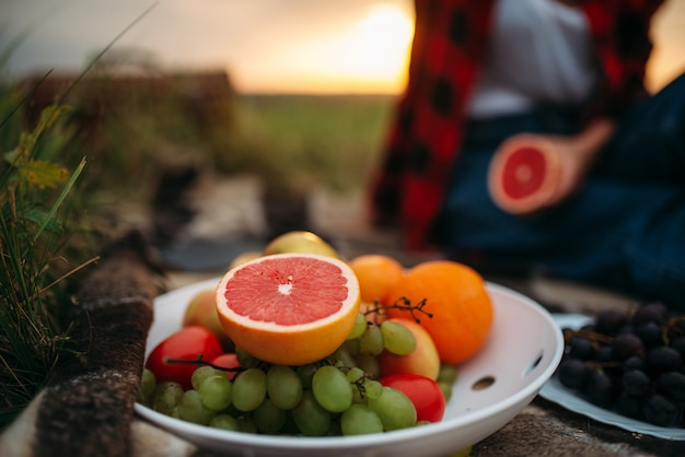 Female person with fruits sitting on plaid, picnic in summer field. romantic junket, happy holiday