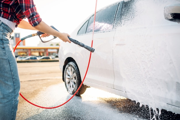 Female person with high pressure water gun in hands wash off the foam from the car. young woman on self-service automobile washing. outdoor vehicle cleaning at summer day