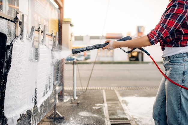 Женский человек с водяным пистолетом под высоким давлением в руках чистит автомобильные коврики, бесконтактную автомойку. молодая женщина на автомойке самообслуживания. уборка автомобилей на открытом воздухе в летний день